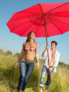 在田里带着遮阳伞的情侣图片