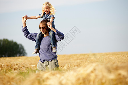 男人和女孩在田里肩并肩图片