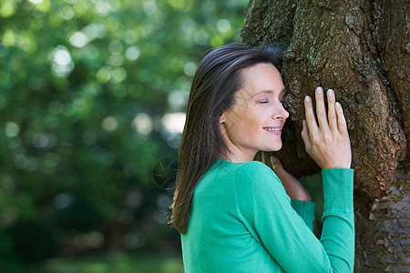 抱着树微笑的女人图片