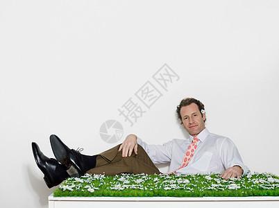 坐在长满草的桌子旁的男人图片