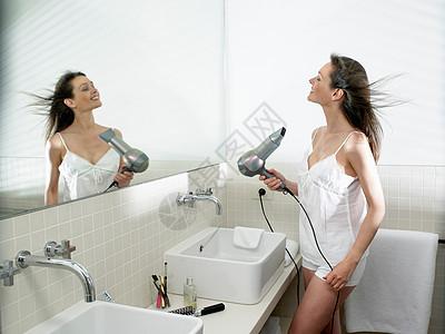 女人在浴室里烘干头发图片