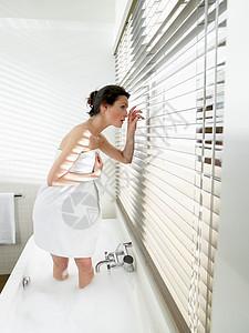 浴缸里的女人透过窗户看图片