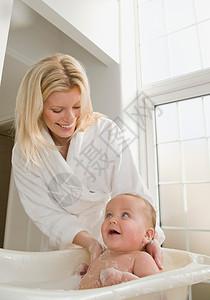 一位母亲给她的男婴洗澡图片