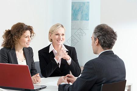 用红色笔记本电脑的商务会议图片