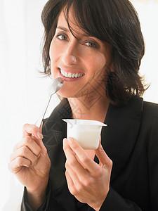 女人微笑着吃酸奶图片