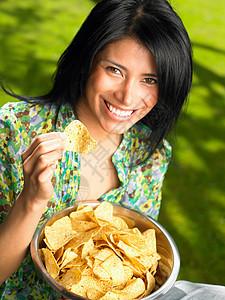 户外吃薯片的女子图片