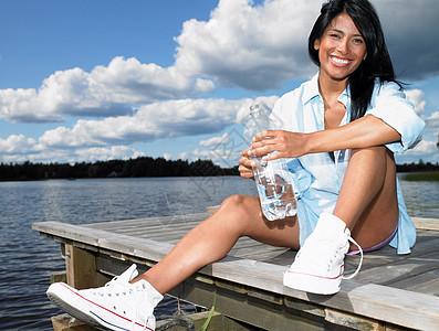 拿着矿泉水瓶微笑的女人图片