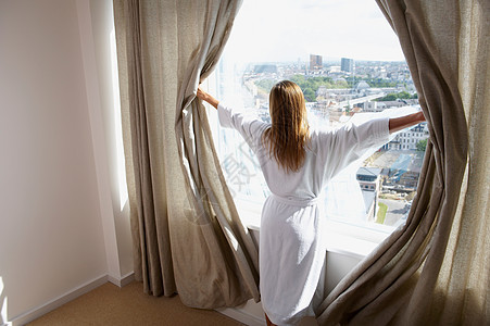 穿着浴袍的女人拉开窗帘图片