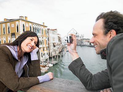 男人在桥上给女人拍照图片