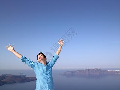 海边伸展双臂的男性图片
