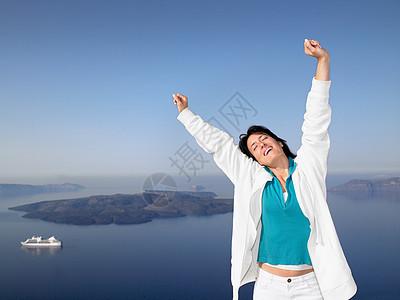 海边伸开双臂的女性图片