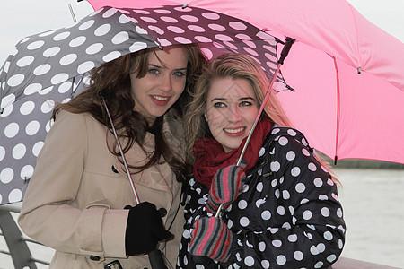 2名打伞的年轻女性图片