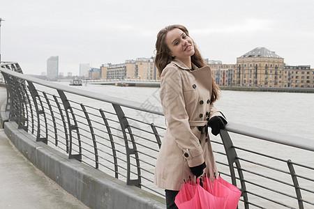 河边带伞的年轻女子图片
