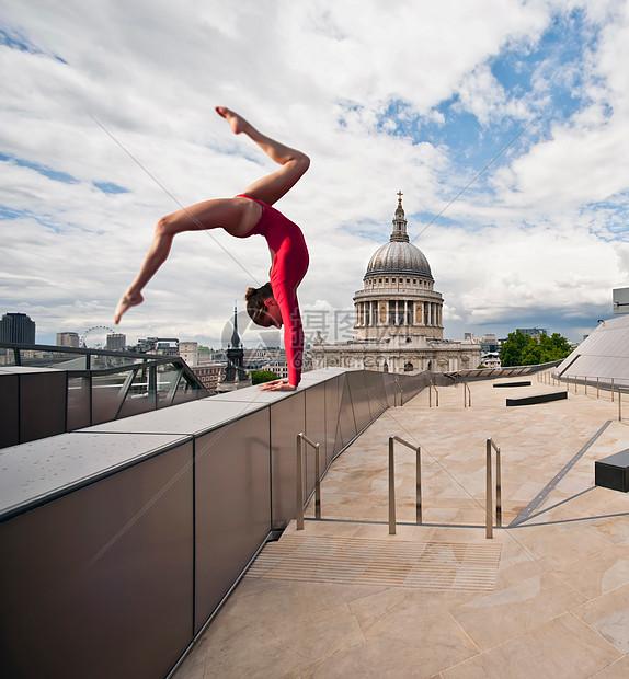 城市屋顶上的体操运动员图片