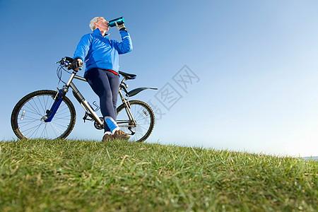 骑自行车时喝水的老人图片