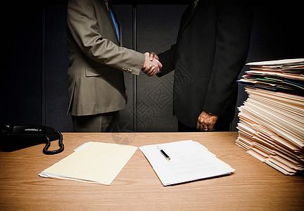 两个商人在办公桌上握手图片