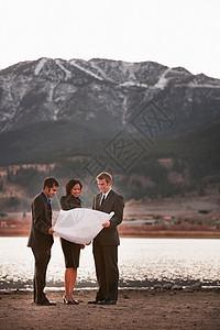 两男一女在湖边检查计划图片