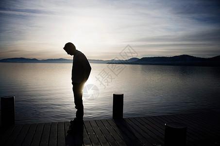 日落时分站在码头上的人图片