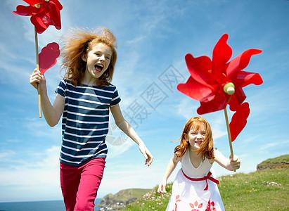 两个女孩在红色风车旁欢笑图片