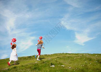两个女孩带着风车在田里跑步图片