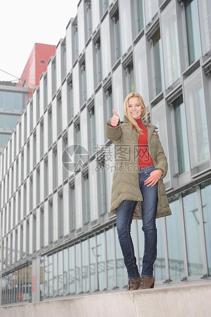 在城市街上竖起大拇指的女人图片