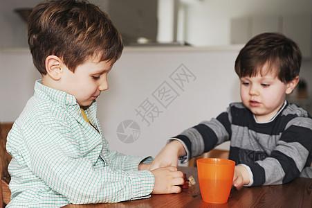 男孩们在桌子上玩糖果图片