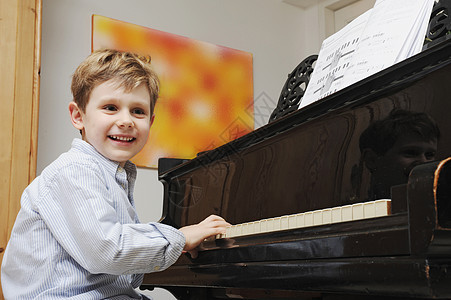 在客厅弹钢琴的男孩图片