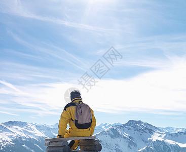 男人坐在山顶长椅上图片