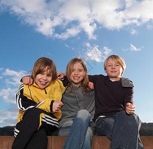 3个孩子坐在矮墙上,微笑着图片