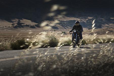 骑在公路上的男性摩托车手图片