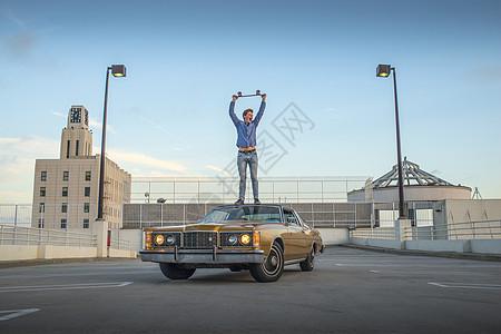 年轻人举着滑板站在车顶的照片图片