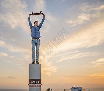 年轻人举着滑板站在柱子上的肖像图片