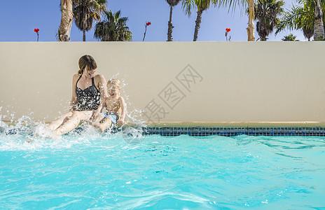 母亲和儿子坐在游泳池里泼水,洛杉矶,加利福尼亚,美国图片