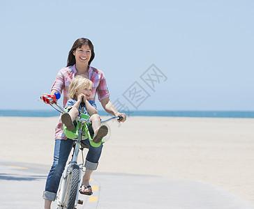 美国加利福尼亚州威尼斯海滩上的妇女和儿子骑车图片