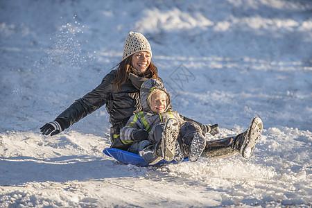 微笑的母子在雪中滑下的照片图片