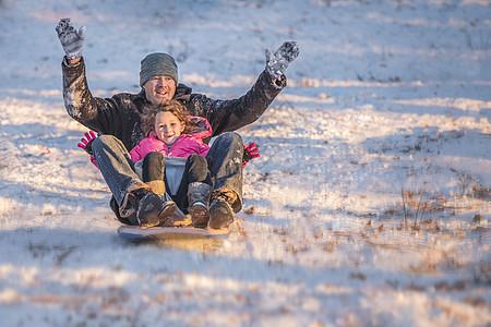 微笑的父女在雪中骑着雪橇下山的照片图片