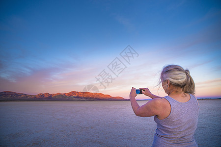 一位女士在智能手机上拍摄盐滩和远处山脉的照片图片