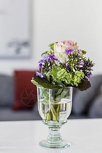 公寓咖啡桌上有切花的酒杯图片