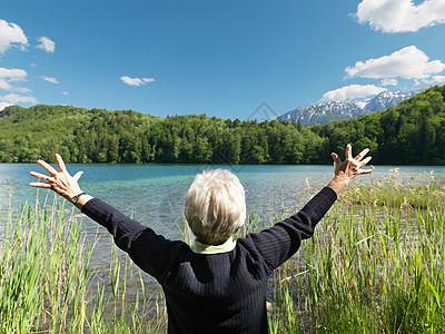 老妇人站在湖边,后视图图片