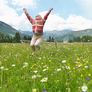 老妇人在花丛中跳跃图片