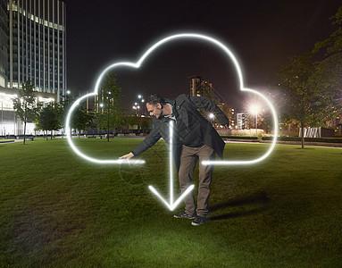 在晚上办公楼外绘制云下载符号的艺术家图片