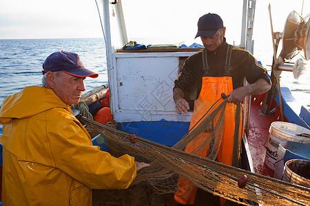 渔民在船上卷起渔网图片