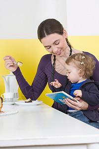 女儿在妇女大腿上吃蛋糕图片