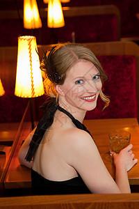 微笑的女人在餐馆喝酒图片