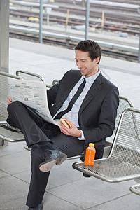 商人拿着报纸坐在椅子上图片