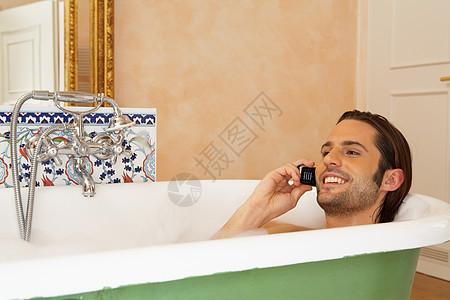 拿着手机在浴缸里微笑的年轻人图片