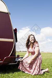 在野外拖车上工作的妇女图片