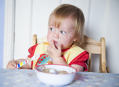 戴围兜的小女孩在桌子边吃饭图片