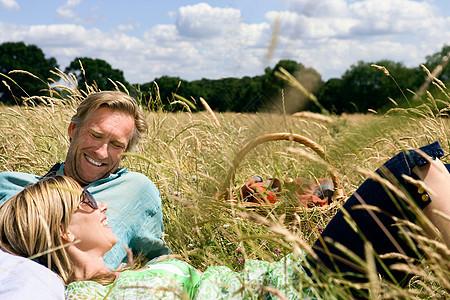 夫妇躺在野餐篮旁的地上图片