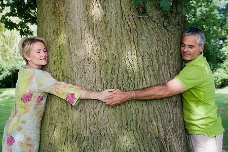 一对夫妇抱着一棵树,特写镜头图片